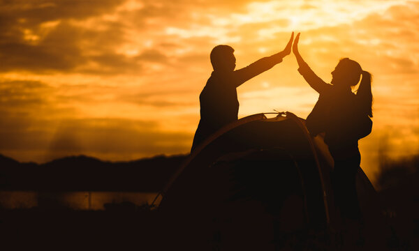 Silhouette Couple Doing High Five While Standing By Tent