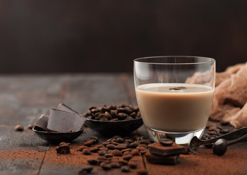 Glass of Irish cream baileys liqueur with coffee beans and powder with dark chocolate and brown cloth on dark wood background.