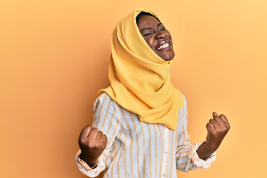 Beautiful african young woman wearing traditional islamic hijab scarf very happy and excited doing winner gesture with arms raised, smiling and screaming for success. celebration concept.