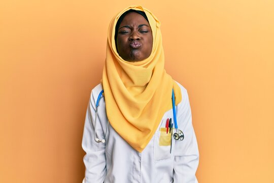 Beautiful african young woman wearing doctor uniform and hijab puffing cheeks with funny face. mouth inflated with air, crazy expression.