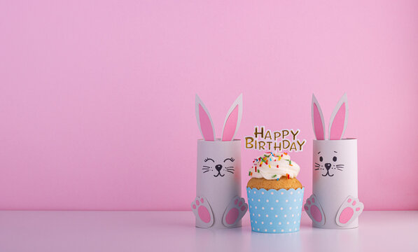 Cute paper rabbits from a roll of toilet paper with the cake on his birthday. Background for the birthday party