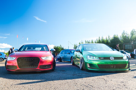 Moscow, Russia - July 6, 2019: Red Audi A4 and Green Golf sports and tuned cars are parked in the parking lot. Alloy wheels and lowered suspension