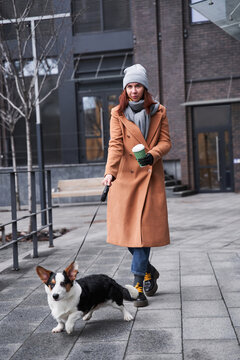 Woman with prosthesis arm holding a leash of her corgi dog