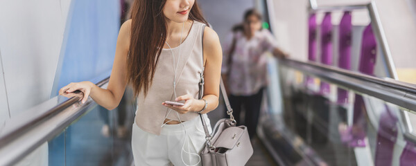 Fototapeta Midsection Of Woman Holding Smart Phone While Standing On Escalator obraz