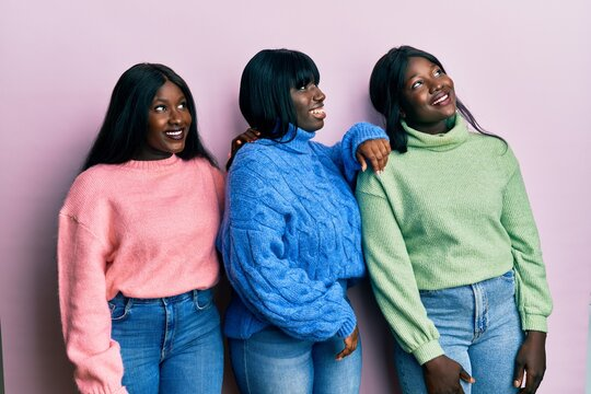 Three young african american friends wearing wool winter sweater looking away to side with smile on face, natural expression. laughing confident.