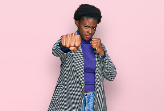 Young african american girl wearing casual clothes punching fist to fight, aggressive and angry attack, threat and violence