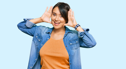 Young beautiful hispanic woman with short hair wearing casual denim jacket smiling cheerful playing peek a boo with hands showing face. surprised and exited Wall mural