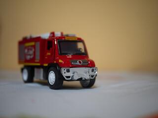 Obraz Zabawkowy wóz strażacki czerwony na żółtym tle - fototapety do salonu