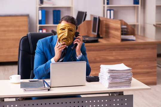 Young male employee wearing sad mask in the office