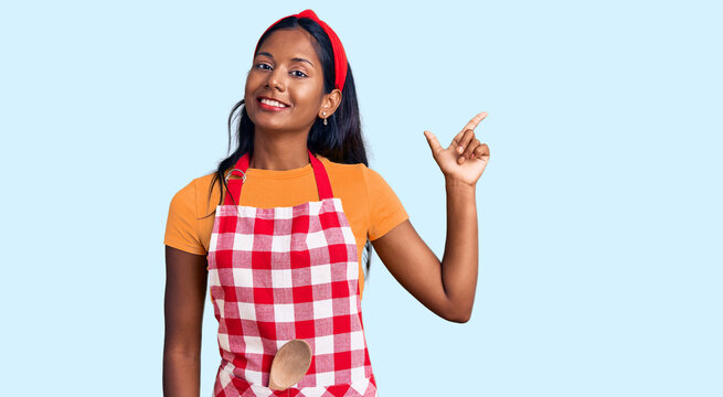 Young indian girl wearing professional baker apron with a big smile on face, pointing with hand and finger to the side looking at the camera.