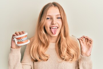 Beautiful young caucasian girl holding invisible aligner orthodontic and braces sticking tongue out...