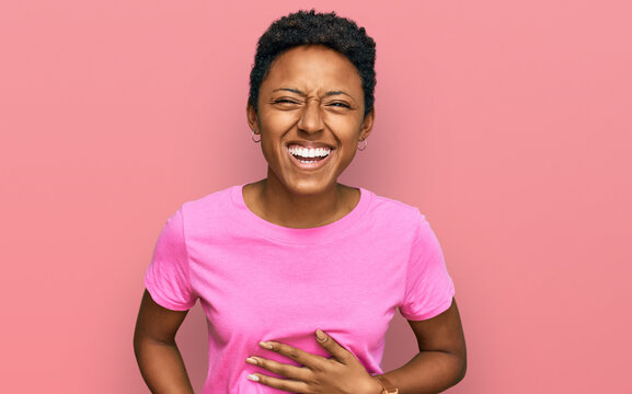 Young african american woman wearing casual clothes smiling and laughing hard out loud because funny crazy joke with hands on body.
