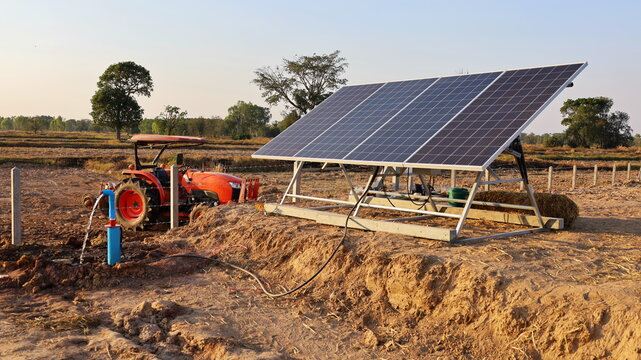 Solar panels and water pumps. The panel converts solar energy or photons into electric energy using submerge pumps for agricultural farms. On the background of the tractor and the sky. Selective focus
