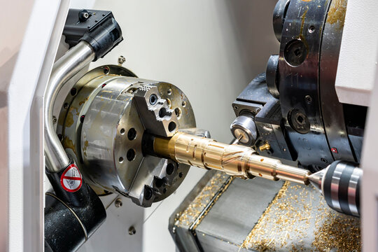 Metal brass workpiece set on spindle chuck of automatic high precision Cnc lathe turning 4 axis machine with function side drill during milling groove by cutting tool in industrial manufacturing