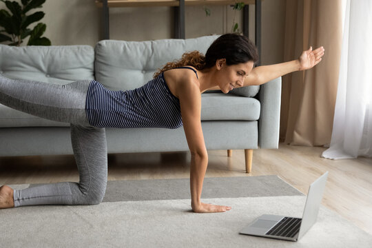 Sporty millennial Caucasian woman watch online sports lesson on laptop doing morning gymnastics in living room at home. Active young female train practice yoga or stretching on webcam on computer.