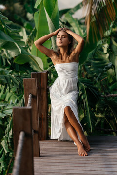 Fashion outdoor portrait of blonde woman, wearing elegant white dress, tropical leaves on background.