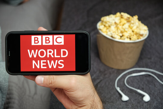 BBC World News on the screen of mobile phone with popcorn and earphones on the background, Close u mans hand holding a smartphone with bbc news app, August 2020, San Francisco, USA