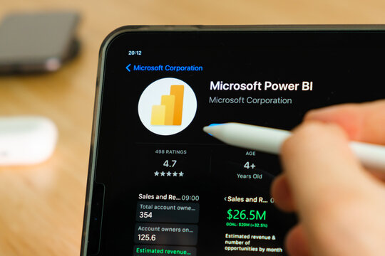 Microsoft Power BI logo shown by apple pencil on the iPad Pro tablet screen. Man using application on the tablet. December 2020, San Francisco, USA.