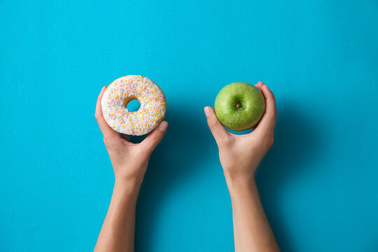 Choice concept. Top view of woman with doughnut and apple on light blue background, closeup