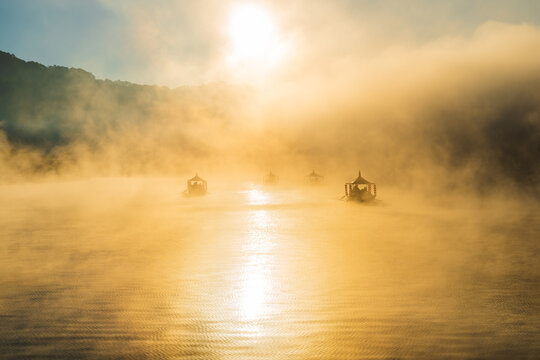 Lake view misty morning of reservoir around with soft mist with yellow sun light in the sky background, sunrise at Ban Rak Thai, Mae Hong Son, northern of Thailand. ,bluerred image