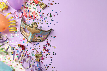 Beautiful carnival mask and party decor on violet background, flat lay. Space for text