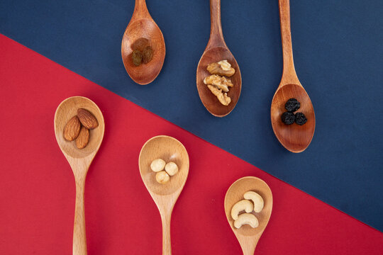 Top view of nuts and raisins assortment in wooden spoons isolated on red-blue background