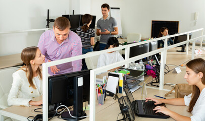 Positive people working with computers and laptops in modern office