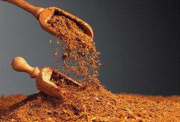 Fototapeta Mixtures of various spices are poured with a wooden spoon. obraz