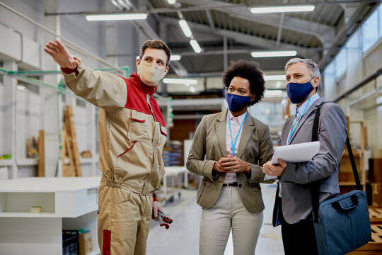 Wood factory worker talking to managers at production facility during COVID-19 pandemic.
