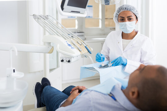 Portrait of focused female dentist with male patient during oral checkup in specialized dental office