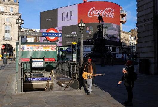 A man with a guitar speaks to a woman at Picadilly Circus in London