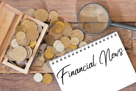 Selective focus of coins, magnifying glass and notebook written with text FINANCIAL NEWS.