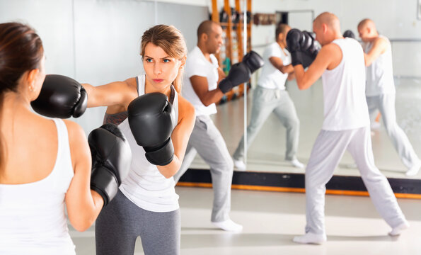 Two diligent efficient serious glad women boxing sparring in the gym