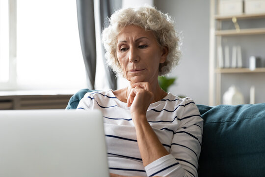 Thoughtful middle aged senior woman looking at laptop screen, reading email with bad news. Frustrated older grandmother thinking on problem solution or having troubles with using computer applications