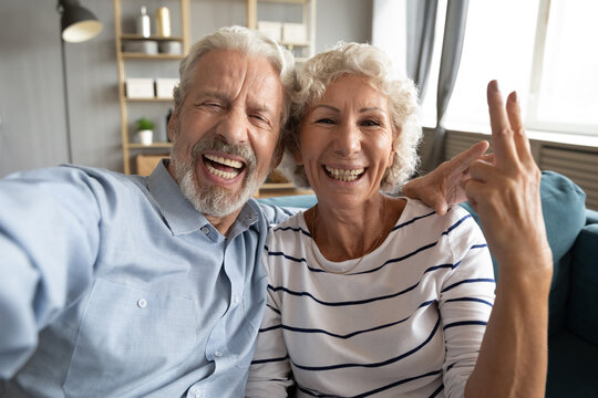 Overjoyed sincere laughing middle aged retired family couple looking at camera, recording funny mobile video or making selfie shot, communicating distantly with family, having fun on weekend at home.