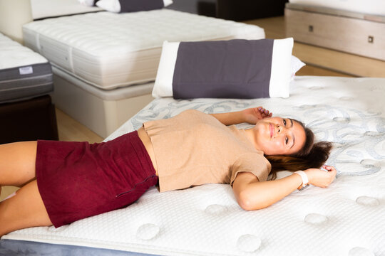 Smiling happy woman testing new mattress in modern furniture store