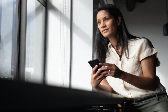 Mxed race businesswoman standing by window using smartphone in modern office