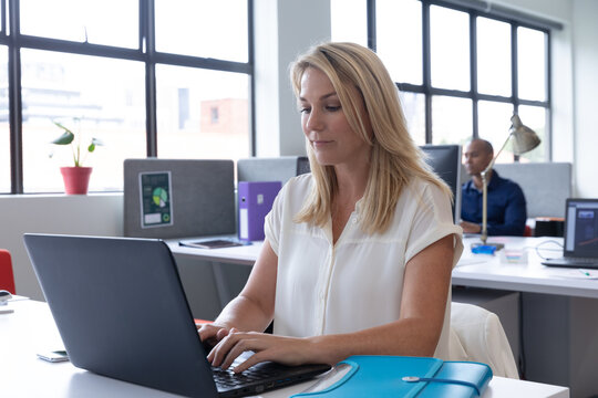 Caucasian businesswoman sitting using a laptop in a modern office