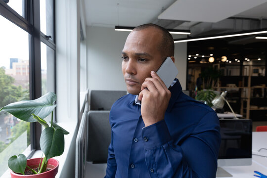 Mixed race businessman standing by window using smartphone in a modern office