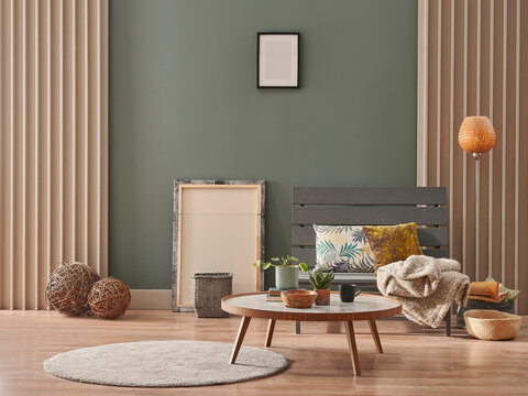 Green wall, grey chair with marble pattern middle table, frame, round carpet, pillow and orange lamp design.