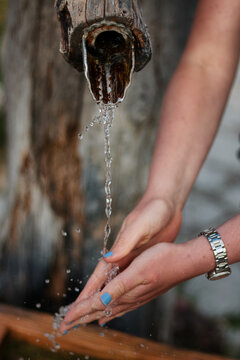 Girl with blue painted fingernails washing her hands in a water trough with crystal clear and sharp water. The picture is taken at a water trough in the bavarian alps, germany.