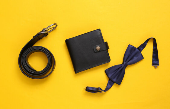 Men's accessories on a yellow background. Leather wallet, bow tie and belt. Top view. Flat lay