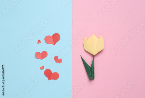 Handmade origami paper tulip and paper cut hearts.on pink blue background. 8 March or mother's day concept. Top view. Minimalism