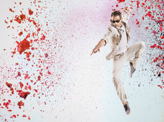 Handsome dancer jumping into the paint splash
