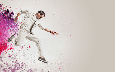 Talented dancer jumping out of paint splash