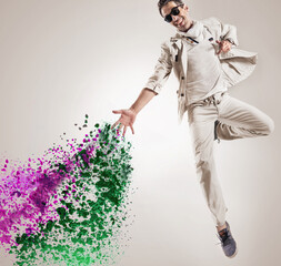 Conceptual picture of a jumping dancer throws paint drops