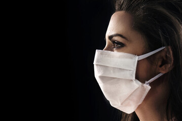 Closeup portrait of a brunette woman wearing a hygienic mask