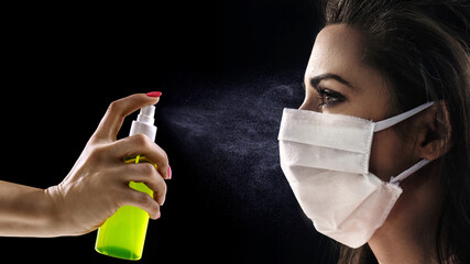 Conceptual portrait of a woman wearing hygienic mask and looking at the antibacterial spray