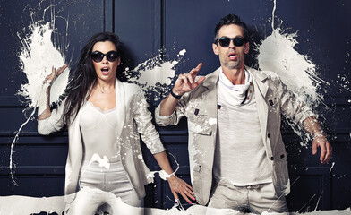 Portrait of an amazed couple covered with white paint