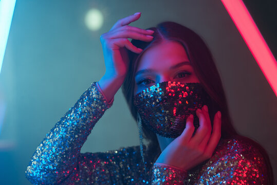 Woman wearing stylish sequin face mask posing, dancing in colorful bright neon uv blue and red lights. Fashion during quarantine of coronavirus outbreak. Copy, empty space for text